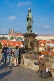 Beggar and tourists on the Charles Bridge in Prague. Prague, Czech Republic - October 6, 2014: Beggar, homeless kneeling begging on the Charles Bridge and royalty free stock image