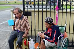 Beggar on wheelchair using cellphone. San Pablo City, Laguna, Philippines - October 20, 2016: Blind Man beside disabled Beggar in wheelchair at Church yard Gate Royalty Free Stock Photo