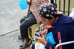 Beggar on wheelchair using cellphone. San Pablo City, Laguna, Philippines - October 20, 2016: Blind Man beside disabled Beggar in wheelchair at Church yard Gate Royalty Free Stock Images