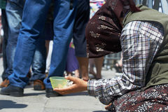 Beggar woman begging for money in the street Stock Image