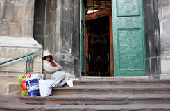 Beggar woman sitting on the doorstep Stock Photos