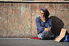 Beggar woman sitting on the floor Stock Photo