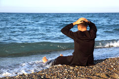 Beggarly barefooted man in suit sits back on coast Stock Image