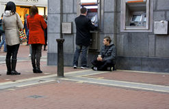 Begger an einer ATM-Maschine Stockfotografie