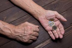 Begging for money. Elderly person Hands of beggar with few coins. The concept of poverty. Begging for money. Elderly person Hands of beggar with few coins. The Stock Photo