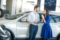 begging tevreden Jonge vrouw die haar echtgenoot bidden om haar een nieuwe auto te kopen royalty-vrije stock afbeelding