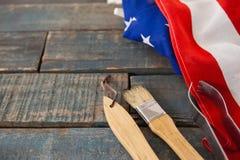Begießen der Bürste und der Zange mit amerikanischer Flagge auf Holztisch Lizenzfreies Stockbild