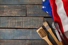 Begießen der Bürste und der Zange mit amerikanischer Flagge auf Holztisch Stockbilder