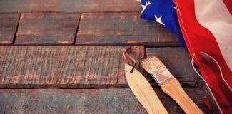 Begießen der Bürste und der Zange mit amerikanischer Flagge auf Holztisch Stockbild