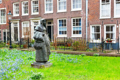 Begijnhof courtyard with statue and historic houses in Amsterdam, Netherlands Stock Photography