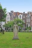 Begijnhof på Amsterdam med den Jesus statyn i mitten som omges av en grupp av historiska byggnader Arkivfoton