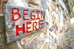 Begin Here Sign on a Rustic Building. `Begin Here` engraved and painted in red on a sign hanging outside an historic farm building on Antelope Island, Utah royalty free stock images