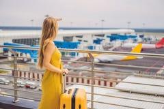 Begin van haar reis De mooie jonge vrouw ltraveler in een gele kleding en een gele koffer wacht op haar vlucht royalty-vrije stock afbeelding