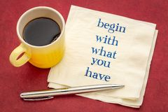 Begin with what you have. Handwriting on a napkin with espresso coffee and pen against red mulberry paper royalty free stock image