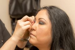 Beginnen der Platzierung der falschen Wimpern in einem Berufsmake-up lizenzfreie stockbilder