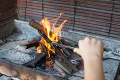 Beginnen des Feuers für Holzkohlen-Grill Arm mit langstieligem Zangen-Se Stockfotografie