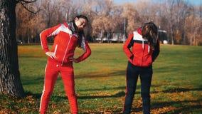 Beginnen junge Frau zwei in den Sportkostümen das Aufwärmen im Park stock video footage