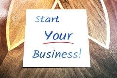 Beginnen Sie Ihre Geschäfts-Anzeige auf dem Papier, das auf Holztisch liegt Lizenzfreie Stockbilder