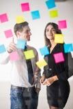 Beginnen Sie oben Unternehmensplanung und Herstellungsorganisation mit jungen Paaren an den Innenschreibensanmerkungen des modern Stockfotos