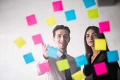 Beginnen Sie oben Unternehmensplanung und Herstellungsorganisation mit jungen Paaren an den Innenschreibensanmerkungen des modern Lizenzfreie Stockfotos