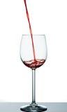 Beginnen Sie, Rotwein in Weinglas zu gießen Lizenzfreie Stockbilder