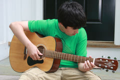 Beginner. Teen is learning to play the acoustic guitar royalty free stock photography