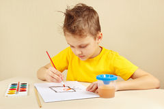 Beginner artist in yellow shirt painting with watercolors Stock Photos