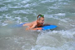Beginner Boogie Boarder. Young boy experiences boogie boarding for the first time at Madeira Beach, Florida. He has a smile plastered all over his face. Blue royalty free stock image