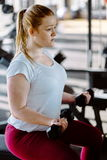 Beginner chubby girl exercising in fitness club. Gym royalty free stock images