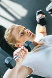 Beginner chubby girl exercising in fitness club. Gym Stock Photography