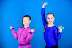 Beginner dumbbells exercises. Children hold dumbbells blue background. Sport for teens. Easy exercises with dumbbell. Sporty upbringing. On way to stronger stock image