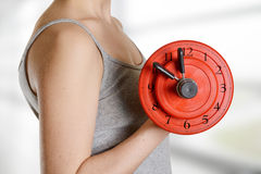 Beginner female athlete holding dumbbell with clock dial. Time f Royalty Free Stock Photo