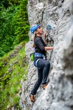 Beginner female climber on top rope, climbing a sport route near Sinaia town, in Bucegi mountains, Romania, on a chilly Spring day. Strong, active girl with stock images