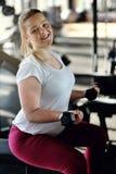 Beginner girl exercising in fitness. Beginner girl exercising with dumbbells Stock Photos