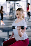 Beginner girl exercising in fitness gym with dumbbells. Beginner girl exercising in fitness gym royalty free stock photos