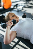 Beginner girl exercising in fitness gym with dumbbells. Beginner girl exercising in fitness gym Royalty Free Stock Images