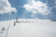 Beginner little girl with skis ascends with ski lift. A Beginner little girl with skis ascends with ski lift Royalty Free Stock Photos