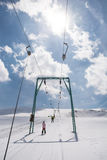 Beginner little girl with skis ascends with ski lift. A Beginner little girl with skis ascends with ski lift Royalty Free Stock Photo