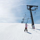 Beginner little girl with skis ascends with ski lift. A Beginner little girl with skis ascends with ski lift Stock Photos