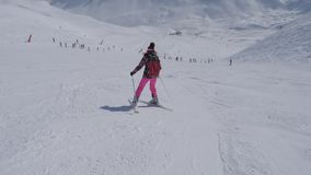 Beginner skier gows down the slope turning left and right. Young beginner skier woman in multicolored coat and pink trousers skis down the slope, turning stock video footage