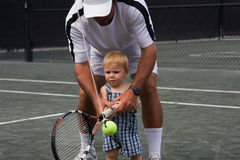 Beginner Tennis Lesson. One year old boy getting his first tennis lesson Royalty Free Stock Image