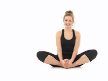 Beginner yoga practice. Young girl smiling, demonstrating yoga pose, full front view, dressed in black, on white background Royalty Free Stock Photography