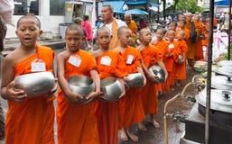 Beginnermonniken die aalmoes op de markt in oude Phuket-stad, Thailand verzamelen royalty-vrije stock foto