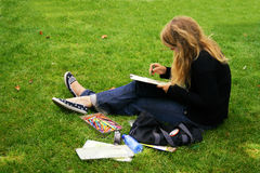 The beginning artist. Draws sitting on a grass in park Royalty Free Stock Images