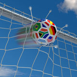Beginning of the championship. Soccer ball with South African flag in the front and destroyed goalnet Stock Photo