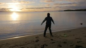 Man rejoices at sunrise. Great start to the day. The beginning of the day. A man meets the dawn on the shore of a beautiful lake. He admires the scenery. 4K stock footage
