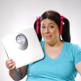 Beginning diet. One young fat girl holding a weight scale Stock Photos