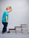 Beginning of education. A kid begins his education represented as a steps made of books Royalty Free Stock Images