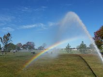 Beginning or end. Firehose stream arching over rainbow Stock Photography