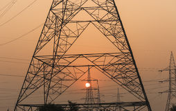 Beginning of the era of technology. Sunrise through poles and wires marks the era of industrial development in a developing country like India Royalty Free Stock Image